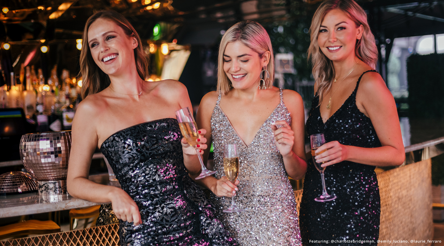Laurie, Charlotte and Emily smiling with cocktails in hand