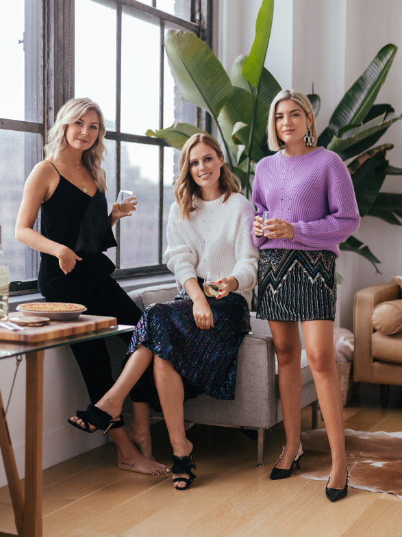 Laurie, Charlotte and Emily posing with drinks in hand at Friendsgiving