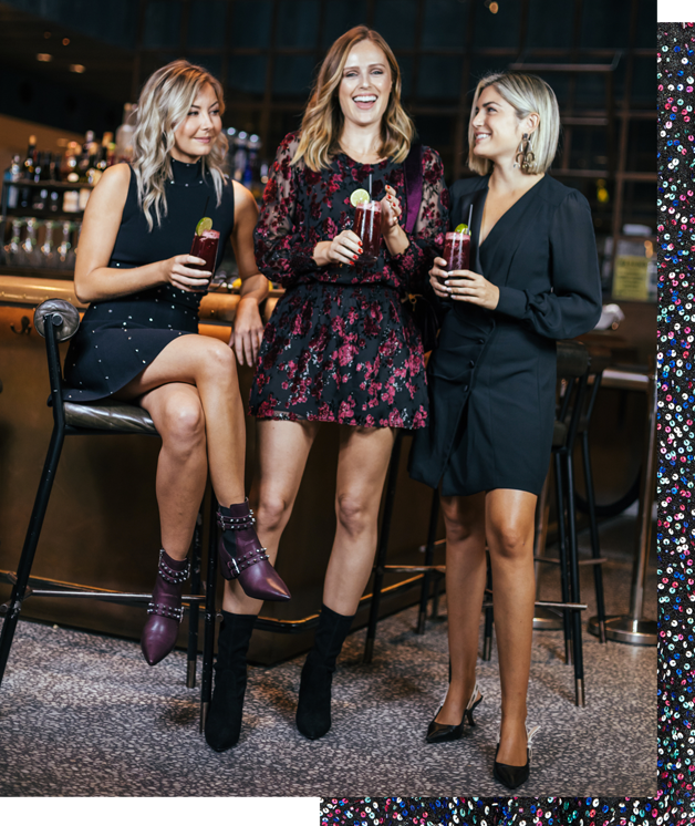 Laurie, Charlotte and Emily posing with drinks in hand at a Bar