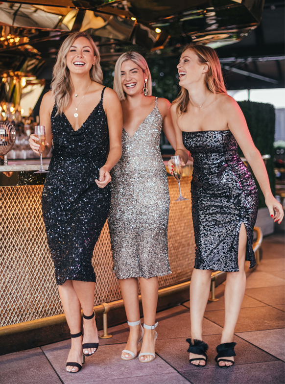 Laurie, Charlotte and Emily laughing with cocktails in hand